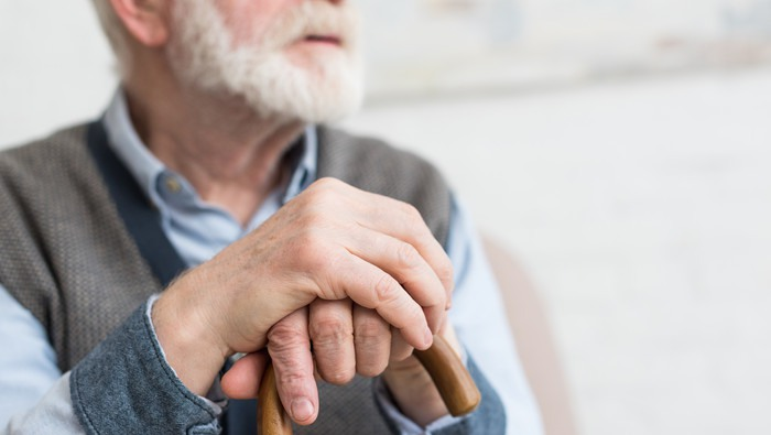 Cropped view of elderly man with walking stick in hands