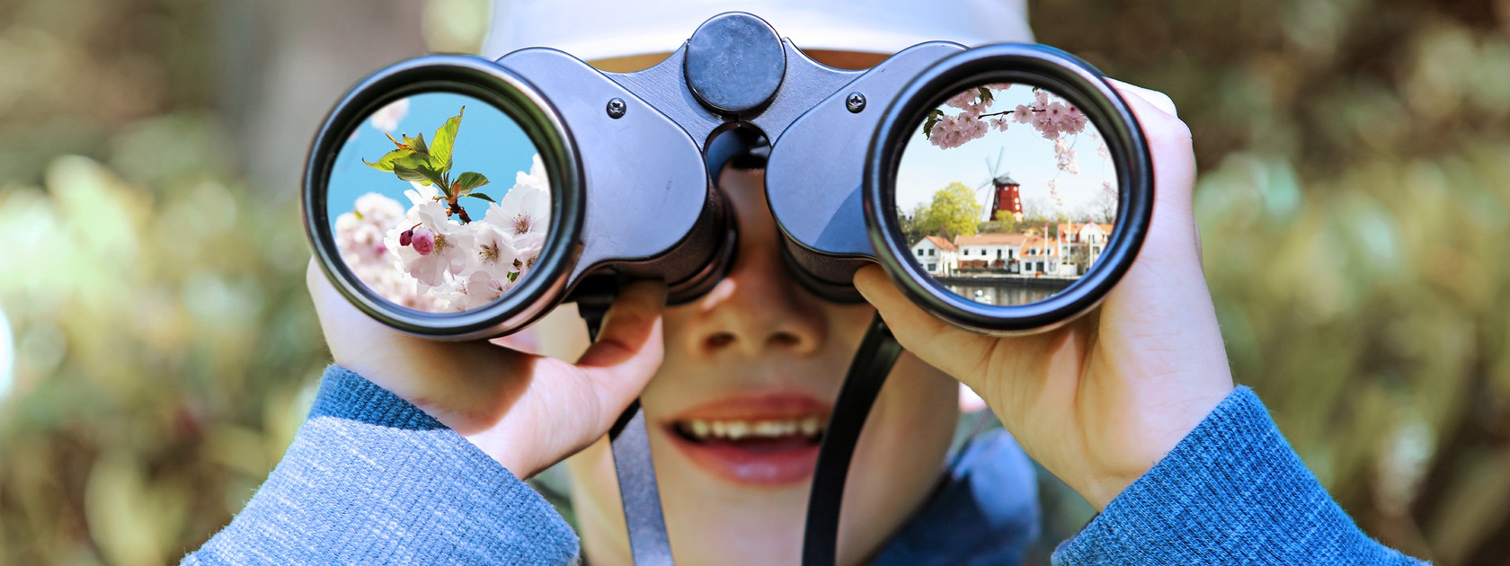 This is a close-up portrait image of a little child who is looking through big binoculars towards the camera. The boy is here seen outdoors in summer and he is wearing a pith helmet and holding binoculars straight towards the camera in such a way that his face is almsot completely covered.